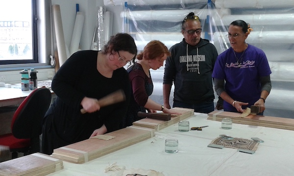 Colour photograph of Megan Creamer (left) taking part in a barkcloth making workshop at the University of Glasgow with Reggie Meredith Fitiao and Uilisone Fitiao (copyright University of Glasgow)
