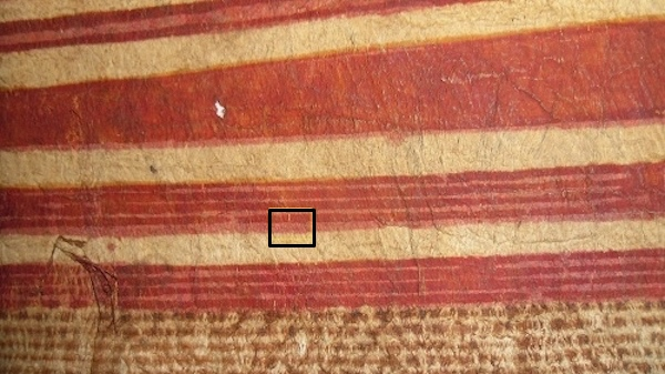 Colour photograph of a detail of the cloth, GLAHM E.667, with a box showing the red-painted area under investigation (copyright University of Glasgow)
