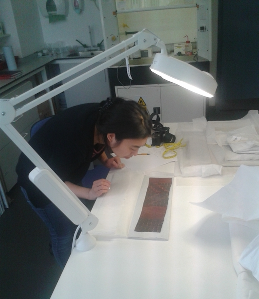 Colour photograph showing Misa Tamura, the barkcloth project research conservator, examining barkcloth for conservation (copyright University of Glasgow)