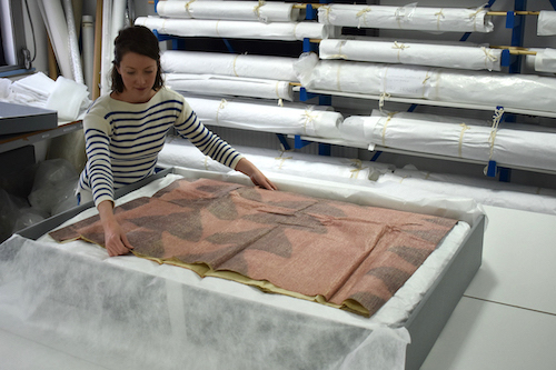 Colour photograph showing a conservation assistant packing a large piece of barkcloth in an acid-free box with rolled pieces shown in storage racks in the background in order to illustrate options for long-term storage of barkcloth (© copyright University of Glasgow)