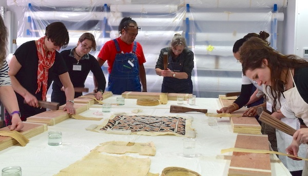 Colour photograph showing participants learning how to beat barkcloth at one of our workshops in 2018 led by Reggie Meredith Fitiao, Professor of Art at American Samoa Community College and siapo maker, and Su'a Tupuola Uilisone Fitiao, contemporary artist and teacher (copyright University of Glasgow)