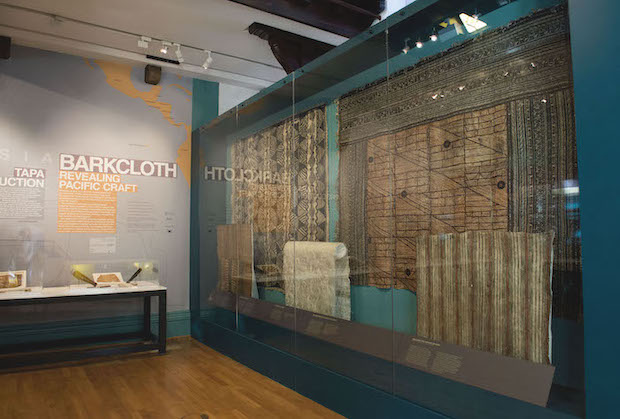 Colour photograph of Selected barkcloths on display in a case as part of the exhibition Barkcloth: Revealing Pacific Craft held at The Hunterian, University of Glasgow from 29 August to 29 November 2019. The introductory text is directly ahead, with a case of barkcloth (Case 5) to the right (copyright The Photographic Unit, The University of Glasgow)