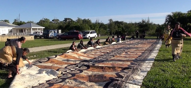 Colour photograph showing members of the women's barkcloth group at Lapaha in Tonga laying out a large ngatu (Tongan tapa) for folding (copyright Vava'u Press Limited)