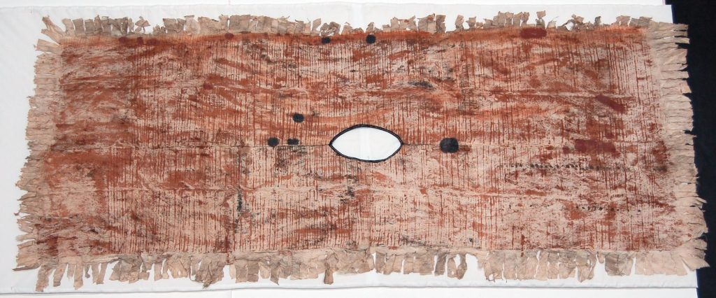 Kew EBC 42861. Colour photograph of a Samoan tiputa or poncho, hand-painted in the tradition of siapo mamanu cloths. This reverse side bears a simple scheme of parallel brown lines showing that it has received at least some rubbed decoration. (copyright Economic Botany Collection, Royal Botanic Gardens, Kew)