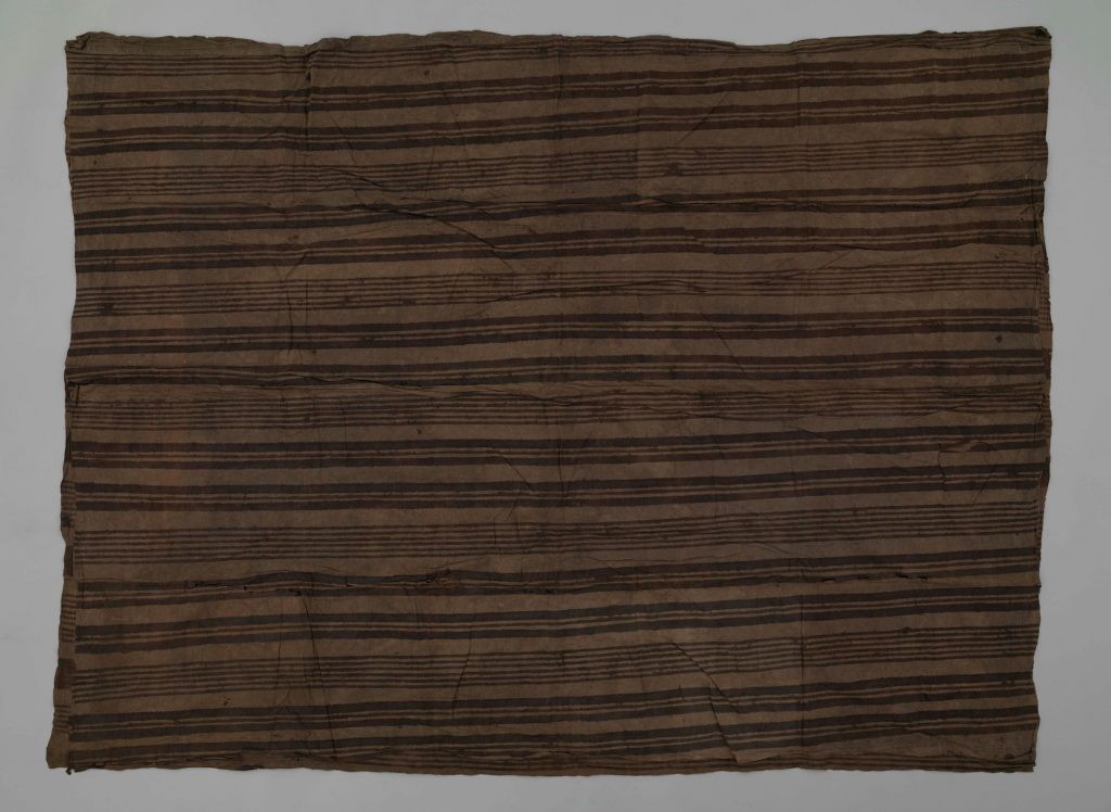 Kew EBC 42890. Colour photograph of a Hawaiian kapa māmaki from 1851, the uppermost layer of a kapa moe bed-cover, as the unpicked stitching along one of its shorter edges indicates. Māmaki (Pipturus albidus ) bast fibres have been shredded and mixed into a base fabric of heavily retted wauke (Broussonetia papyrifera). It is hand-painted with stripes of a deep brown colourant which has caused the deterioration of the cloth in these areas. (copyright Economic Botany Collection, Royal Botanic Gardens, Kew; hotograph supplied by The Photographic Unit, The University of Glasgow)