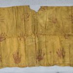 Kew EBC 42947a. Colour photograph of a Tahitian tiputa poncho of the 1860s, collected by HRH Alfred, Duke of Saxe-Cobourg and Gotha, on the voyages of HMS Galatea. Immersion dyed a dark orange-yellow colour closely associated with turmeric, and over-printed throughout with hand-prints in a red pigment. (Copyright Economic Botany Collection, Royal Botanic Gardens, Kew)