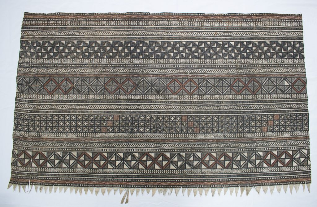 The Hunterian GLAHM E.537. Colour photograph of a sample of a late 19th century Fijian masi kesa fabric, intricately stencilled in black, red and brown. This sample is a small section of the outer border of a much larger fabric (copyright The Hunterian, University of Glasgow)