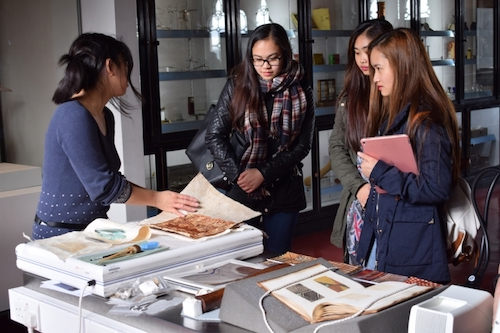 Colour photograph of Research Conservator, Misa Tamura, discussing barkcloth conservation with a group of students during European Researchers' Night in the Hunterian Museum in 2016 (copyright University of Glasgow)
