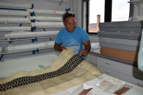 Colour photo of Ngaa Kitai Taria Pureariki, from Aitutaki in the Cook Islands, examining part of a maro loincloth (GLAHM E.670) from Rarotonga, the largest of the Cook Islands (copyright University of Glasgow)