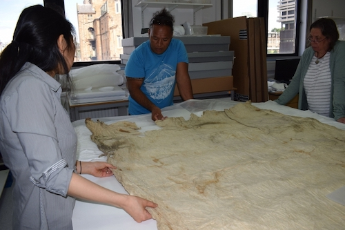 Colour photograph of the project's Research Conservator, Misa Tamura, with Dr Michaela Appel, Curator at The Museum Fünf Kontinente in Munich and Ngaa Kitai Taria Pureariki, from Aitutaki in the Cook Islands. They are looking at a plain, Tahitian cloth, GLAHM E.457/8 (copyright University of Glasgow)
