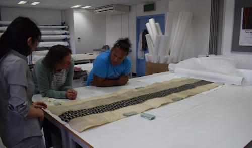 Colour photo of the project's Research Conservator, Misa Tamura, with Dr Michaela Appel, Curator at The Museum Fünf Kontinente in Munich and Ngaa Kitai Taria Pureariki, from Aitutaki in the Cook Islands. They are examining part of a maro loincloth (GLAHM E.670) from Rarotonga, the largest of the Cook Islands (copyright University of Glasgow)