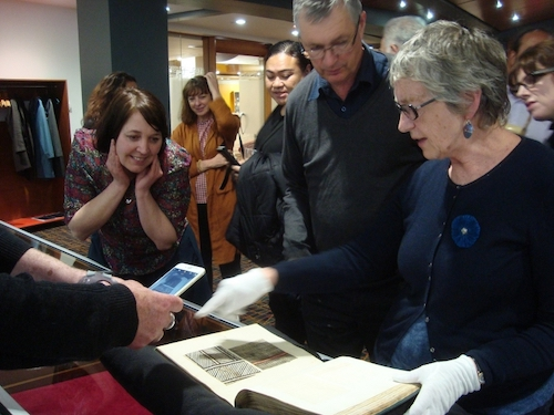 Colour photo of participants attending an evening meeting at Auckland Central Library who were able to see one of the treasures of Auckland Libraries, their copy of the Alexander Shaw book of 18th century tapa samples (copyright University of Glasgow)
