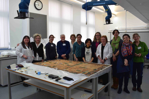 Colour photograph of delegates at a barkcloth workshop for conservators held at the University of Glasgow. The workshop was led by the project's Research Conservator, Misa Tamura (7th from left). Student volunteer Kim Tourret is on the left. (copyright University of Glasgow)