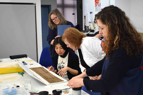 Colour photograph showing a group of workshop participants discussing the barkcloth sample GLAHM 596/9 from the Hunterian collection with Misa Tamura, the project's research conservator (copyright University of Glasgow)