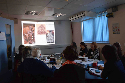 Colour photograph of a group of workshop participants looking at a powerpoint presentation putting barkcloth production in the context of its use and significance (copyright University of Glasgow)