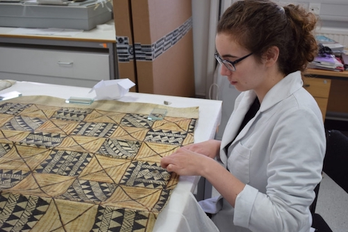 Colour photograph showing a conservation student, Beth Knight, working on a Samoan siapo tasina cloth, GLAHM E.592/1 (copyright University of Glasgow)