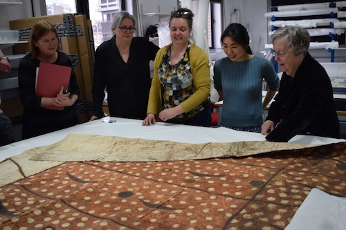 Colour photograph of members of the project team and advisory panel: Julia Gresson, Sherry Doyal, Monique Pullan, Misa Tamura and Dr Adrienne Kaeppler, looking at a Tongan cloth with unusual decoration, GLAHM E.595 ( University of Glasgow)