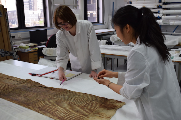 Colour photograph showing project team members, Margaret Smith and Misa Tamura, at work in the conservation laboratory taking samples of a barkcloth object for analysis (copyright University of Glasgow)